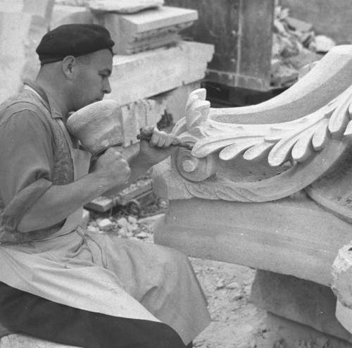 A stone mason carving a block of stone