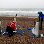 Coastal team members setting up the portable devices used to measure sediment transport on mixed sand and gravel beaches at Minsmere, East England, UK (more info about the device here: https://doi.org/10.1016/j.coastaleng.2019.103580)