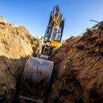 Mini Excavator. Excavator digs the foundation for the house. Photo credit Avalon_Studio.