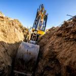 Mini Excavator. Excavator digs the foundation for the house. Photo credit Avalon_Studio