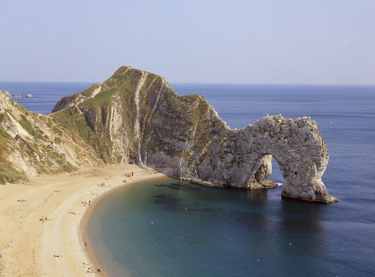 Durdle Door: an arch of rock protruding into the sea by a sandy beach