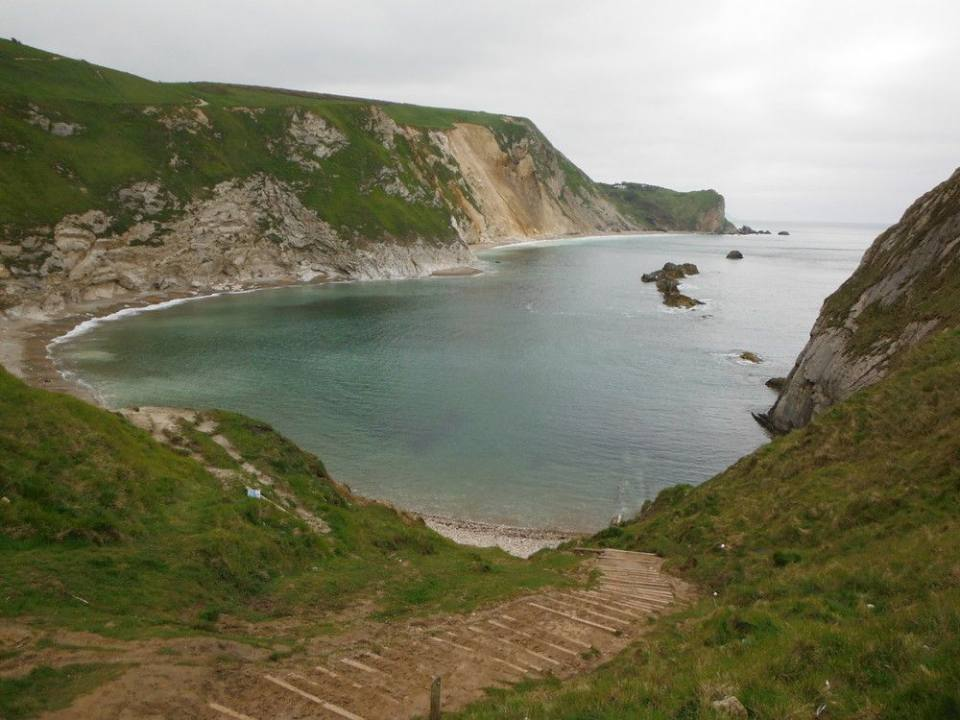 Man o' War Cove and St Oswald's Bay, west of Lulworth, Dorset: a wide, crescent-shaped bay with white cliffs
