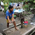 A wom,an pumping water from a public well in a street