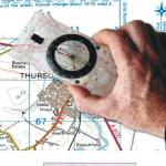 A hand holding a compass over a map