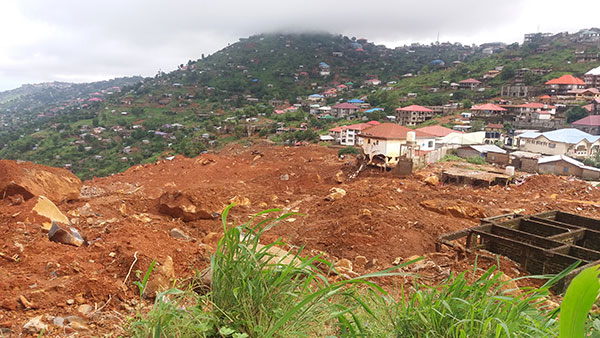A landslide consisting of orange-brown soil has run down a green slope, covering and damaging white buildings