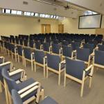 Chairs lined up inside a large room facing a smartboard on the wall at the far end