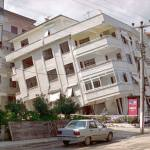 A white, four storey building in Izmit, Turkey, leans at a dangerous angle due to an earthquake. There is a road next to it with other buildings that are not affected.