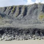 Gullies in a cliff face made of dark-coloured rock, forming a landslide on a beach