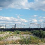 A large, unused, urban brownfield site with open land covered in cracked, overgrown concrete awaiting development in Leeds, England. © Adobe Stock, 282946502.