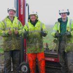 Three geologists wearing hi-vis gear and covered in mud, giving the camera a thumbs-up