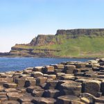 The Giant's Causeway in Northern Ireland. Hexagonal blocks of brownish grey rock in the foregroud, with seain the biddle ground and a high cliffs of basailt columns and green grass in the background.